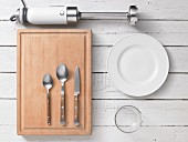Assorted kitchen utensils: a wooden chopping board, cutlery, crockery and a stick blender