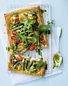 Puff pastry tart with green asparagus, ricotta, cherry tomatoes, bacon and rocket