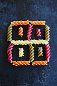 Colourful fusilli arranged to form a square pattern