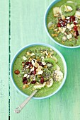 A spinach, banana and oat smoothie bowl topped with kiwi, lingonberries, nuts and chia seeds