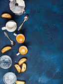 Coffee espresso in cups with italian cantucci, cookies and milk in jug over dark blue background