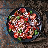 Black plate with sliced different tomatoes, red onion, balsamic sause, parsley and feta cheese salad