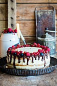 A semi-naked cake with vanilla cream, fresh berries and chocolate ganache