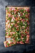 Pizza with Parma ham and herbs on a baking tray
