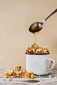 Prepared caramelized sweet popcorn served in vintage white enameled mug