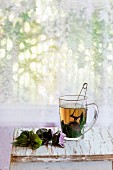 Glass cup of hot herbal tea with bunch of fresh violet basil, served with vintage tea-strainer on old wooden stool