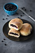 Jagodzianki (Polish buns with a blueberry filling) on a black plate