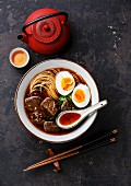 Asian noodles in broth with slow cooked Beef and Egg on dark background