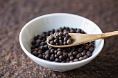 Allspice with a wooden spoon in a bowl