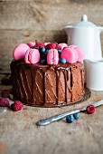 Chocolate cake with dripping chocolate ganache, fresh berries and homemade pink macarons