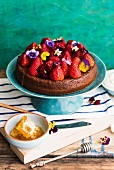 Honey cake with strawberries and horned pansies