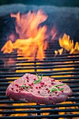 A fresh steak seasoned with pepper and rosemary on a grill rack with fire
