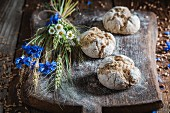 Healthy wholemeal bread rolls with ears of corn and field flowers on a wooden board
