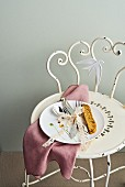 East Friesian cutlery tied together with lace ribbon on a porcelain plate on vintage metal chair