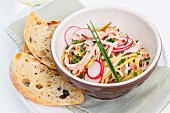 Sausage salad with cheese and radish served with olive bread