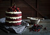 A red velvet cake with berries and cherries