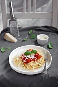 Spaghetti with tomato sauce garnished with grated parmesan and fresh basil leaves