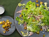 Smoked trout on a green salad with potato croutons and horseradish sauce
