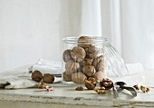Walnuts in and next to a glass jar with a nutcracker on a rustic kitchen table