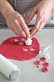 Flowers being cut out of rolled-out marzipan