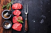Raw fresh marbled meat Steaks with seasonings and meat fork on dark marble background