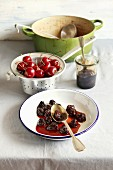 Cherry jam on a plate, fresh cherry in aluminum colander and dutch pot with cherry jam on background