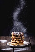 White plate with homemade belgian waffles with Sifting sugar powder over black background