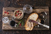 Glass jars of chicken liver pate with blackcurrant jam, pomegranate grain and sliced bread