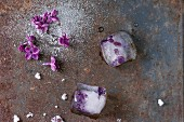 Ice cubes with lilac flowers, white sugar and sugared lilac flowers