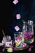 Ice cubes with flowers falling into glass of lilac lemonade with lemon