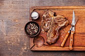 Grilled T-Bone Steak with salt and pepper on meat cutting board on dark wooden background