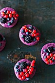 Vegan raw berry tarts on a black background