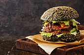 Roast beef Burger on sesame bun with sliced Pastrami on black background