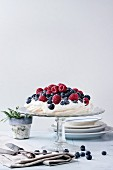 Vintage cake stand with Meringue dessert Pavlova with fresh blackberries and raspberrie