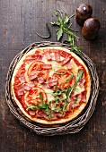 Pizza with ham, tomatoes and rucola