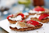 Bruschetta with fresh cream cheese, anchovies, peppers, oregano and lime zest