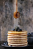 Pancakes with fresh blueberries in blue ceramic plate, and flowing honey from wooden honey dipper
