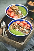 Green smoothie bowls with fresh strawberries, granola, chia and pumpkin seeds, dried fruit and nuts