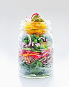Vegetable salad with peas, avocado, radishes, bread and spinach in a glass jar