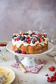 Vanilla bundt cake with cream cheese icing and berries on a cake stand