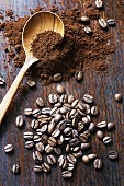 Coffee beans and ground coffee with a wooden spoon