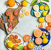 Natural fresh citrus fruits on wooden rustic board, colorful ceramic plates over grey marble table background
