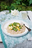 Pearl barley risotto (orzotto), served with yellow zucchini, broad beans and fresh thyme. Dish of Italian cuisine
