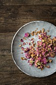 Dried edible pink rose petals on a grey plate on a wooden surface