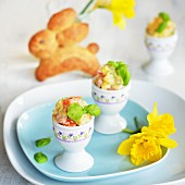 Potato salad with carrot, apple, peas and mayonnaise served in egg cups, with a yeast bread Easter bunny and daffodils in the background