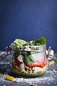 Salad with fusilli, pesto, red pepper, spinach, chicken and parmesan in a glass jar
