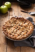 Apple pie with a dough lattice and pastry roses in a tin
