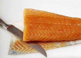 Haut und Fettschicht mit Messer vom Lachsfilet entfernen
