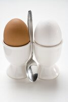 Brown and white eggs in eggcups, spoon between them