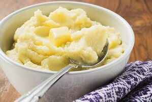 Mashed potato with butter in white bowl with spoon